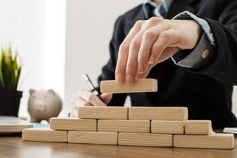 empresário empilhando blocos de madeira representando cálculo ROI